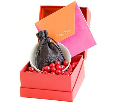 Photo of the Forty Beads gift set: an open red box with forty red beads, a white bowl and a leather drawstring pouch inside.