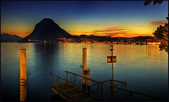 Lago di Lugano, Switzerland (Wolfgang Staudt) Tags: sunset sun mountain lake water reflections lago lights schweiz switzerland tessin see pier ticino nikon wasser shadows nightscape nacht availablelight tripod saturday reflexions riflessi lugano hdr highdynamicrange steg stativ lakelugano lagodilugano supershot abigfave wolfgangstaudt colorphotoaward overtheexcellence nikond300 goldstaraward