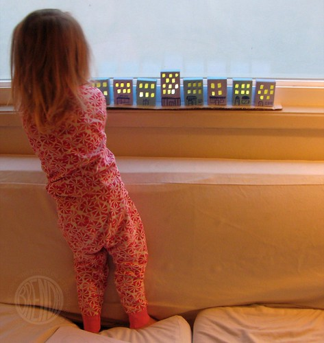 child standing on couch looking at paper village craft