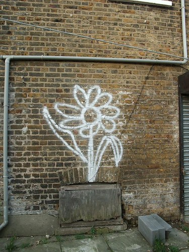 graffiti -- white daisy on a brick wall