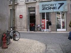 Uma loja de desporto, vende bicicletas, mas não há estacionamento para quem lá vá de bicicleta...