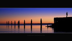 Waiting For A Friend (Garry - www.visionandimagination.com) Tags: morning blue red orange reflection nature water hat silhouette canon landscape person dawn pier twilight purple oz pano australia brisbane hues 5d outline aus stumps sandgate moretonbay waitingforafriend shorncliffe shorncliffepier impressedbeauty wwwvisionandimaginationcom