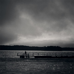 solitude (saicode) Tags: blackandwhite cloud water island evening dock waiting solitude waves alone cloudy horizon coastal squareformat seashore justbeforesunset