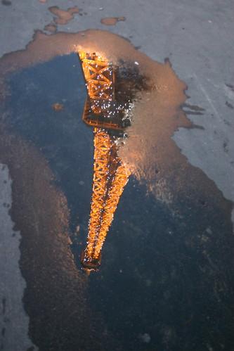 Spiegelung des Eiffelturms in einer Lacke. / Eiffel Tower