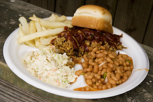 fries, a roll, bbq pork, beans, and coleslaw