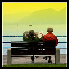 Bad financial News? (Barry McGrath) Tags: sunset people italy lake mountains water canon landscape lago eos reading chair holidays seat september monte 2008 30d iseo artisticexpression lakeiseo aplusphoto barrymcg bazzymcg iseola