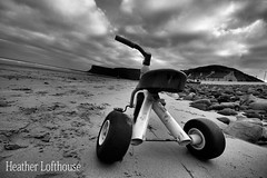 Born to be wild (Flamelillyfox) Tags: sky bw cliff abandoned beach broken bike kids toy seaside sand rocks tricycle horizon wideangle shore rubbish saltburn theship grot wonk huntcliff bwdreams