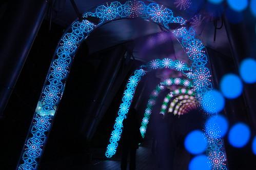 Fotografía de un tunel repleto de arcos con luces azules en la oscuridad, algunas de ellas desenfocadas