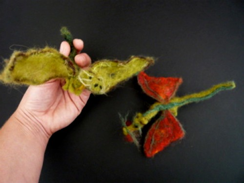 two needlefelted dragons and a hand