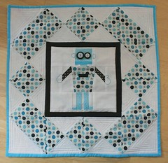 a square piece of quilting, near the border there are rectangles and squares set at diamond angles, then a thick black square boarder, and in the center is a quilted robot
