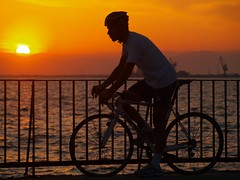 riding towards the sun (maios) Tags: travel sunset sea sky cloud sun man water bike metal port greek boat photo europa europe flickr mediterranean ship photographer horizon hellas greece riding macedonia thessaloniki fotografia umbrellas salonica manikis maios iosif   heliography    mywinners  zogolopoulos                iosifmanikis