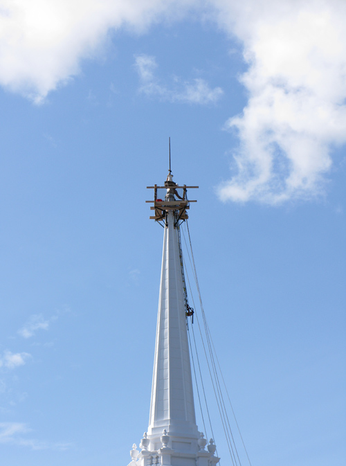 a man works atop a steeple in Littleton, New Hampshire