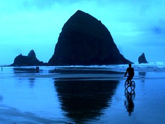 Michael Riding to Haystack Rock (Merelymel13) Tags: ocean blue reflection water bike bicycle rock oregon michael waves august cannonbeach haystackrock 2008 soe naturesfinest bluehues ultimateshot imadeittoexplore august2008