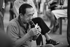 Street hawker I (Sean Lowcay (sealow08)) Tags: street people bw man slr film night 35mm singapore asia minolta minoltax700 microphone hawker x700 fujifilmsuperiaxtra400