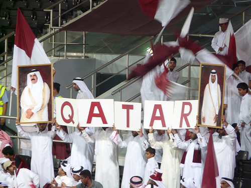 Enthusiastic football supporters wave the national flag of Qatar.
