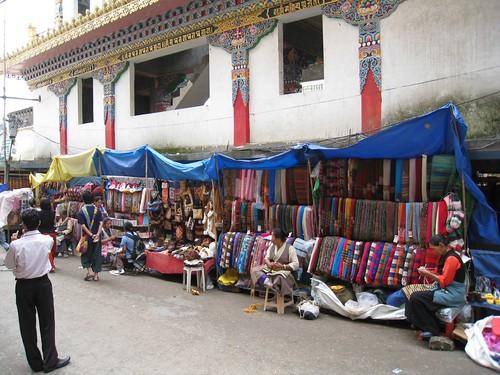 Tibetan women knit beside their street stalls