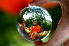 Buddhist monk in a crystal ball, Laos (kees straver (will be back online soon friends)) Tags: travel light orange macro reflection glass ball temple bravo asia crystal buddhist religion monk buddhism fortune sphere refraction laos luangprabang crystalball buddhistmonk abigfave keesstraver