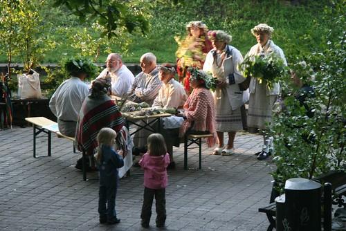 Ältere Menschen mit Blumenkränzen und auf einer Bank