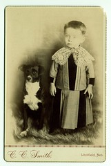 Child with lace collar, posed with dog
