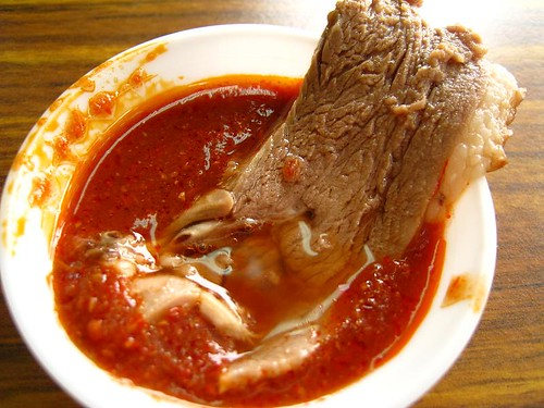 Slice of duck swimming in chili sauce