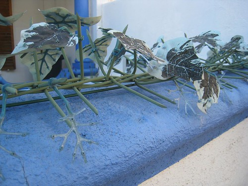 Plastic leaves are used in an attempt to soften the look of barbed wire outside a business