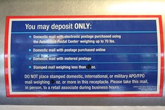Post Office Self Service Kisosk sign. This reads: You may deposit ONLY: Domestic mail with electronic postage purchased using the Automated Postal Center weighing up to 70 lbs. Domestic mail with postage purchased online. Domestic mail with Metered postage. Stamped mail weighing less than 13 oz. Do not place stamped domestic, international, or military APO/FPO mail weighing 13 oz or more in this receptacle.  Please take this mail, in person, to a retail associate during business hours.