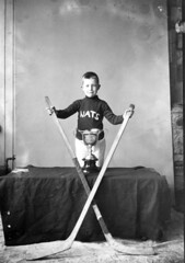 Nationals Hockey Team [boy with hockey sticks and trophy]