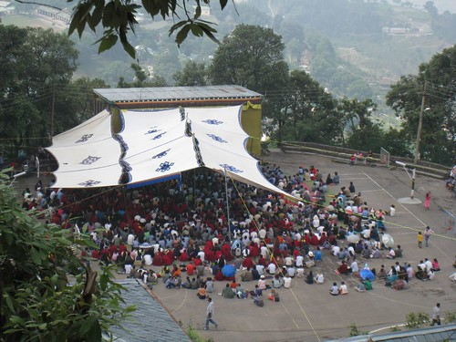 A crowd of tourists, locals and monks watch the video feed