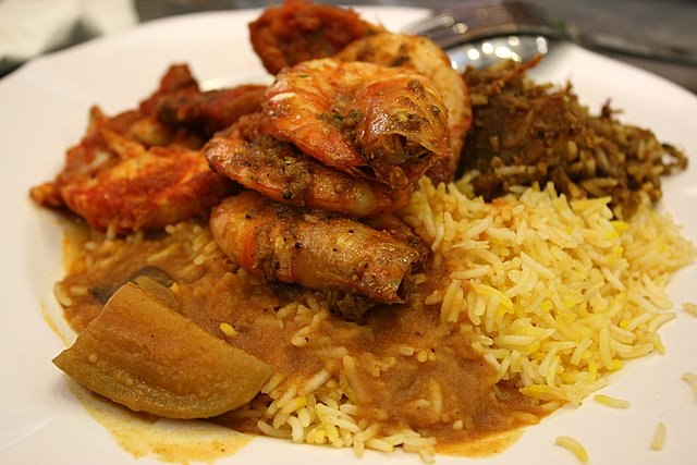 Platter of prawn curry on briyani rice, with ayam masak merah, vegetable dhal curry and mutton rendang
