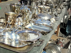 a display of lots of sterling silver items set out on a table at an antique sale