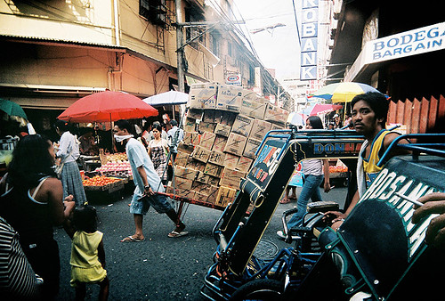Manila man transporting heavy boxes of merchandise along  a busy Divisoria market street  Buhay Pinoy Philippines Filipino Pilipino  people pictures photos life Philippinen