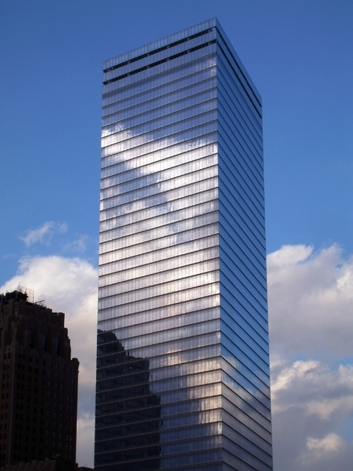 a building in lower Manhattan reflects clouds, NYC