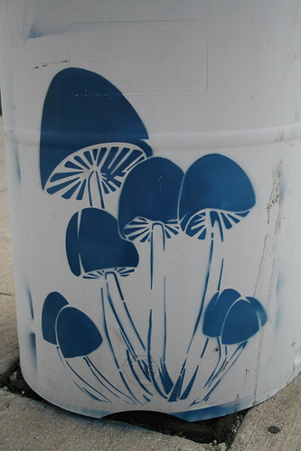 stencil graffiti of a bunch of mushrooms growing out of the concrete, painted at the base of a  post