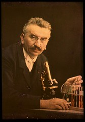 Louis Lumiere with microscope and test tubes