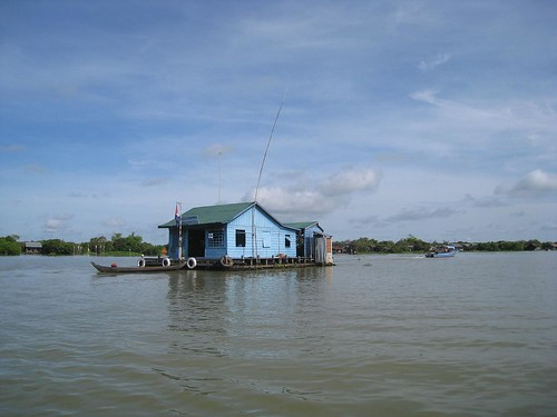 A floating house is relocated via longboat