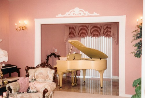 pink walls; victorian chair; light wood piano; pink and white curtains