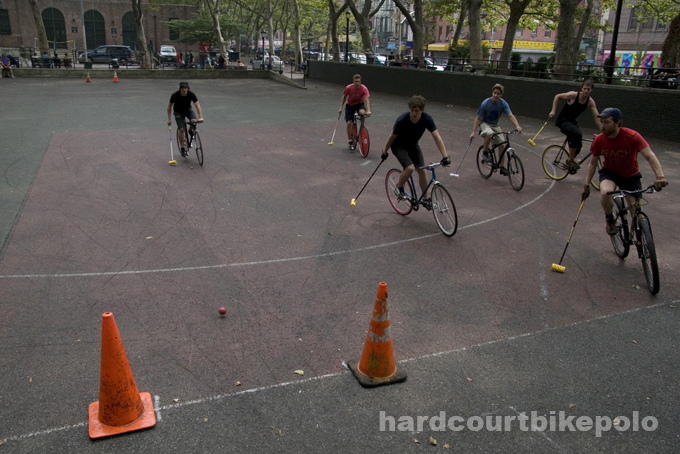 7-6-2008 street hockey ball rolls in as six bike polo players watch a shot on goal