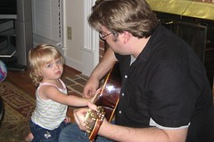Cate helping her daddy play guitar