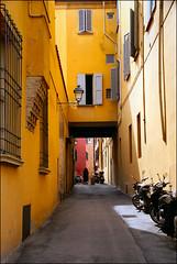 a typical italian street....... (atsjebosma) Tags: street windows italy woman lamp yellow italian perspective scooter pointofview ramen bologna shutters colourful soe straat luiken abigfave