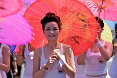 Parasols (Gene Fama) Tags: street girl festival losangeles crowd tshirt pedestrian fair stranger parade parasol hollywood tanktop stolen losfeliz streetfair thaitown wifebeater clich stockphotography thainewyear thaigirl redandpink canonef85mmf12lii