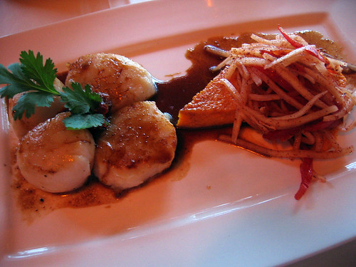 Seared sea scallops with orange miso sauce, bell pepper and saffron polenta