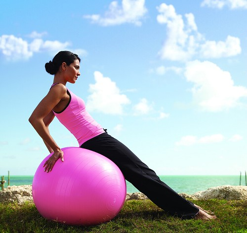 A woman sitting on a pink exercise ball.
