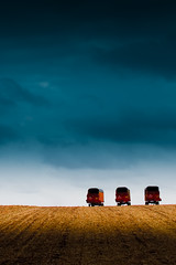 I Saw Three Trailers Come Rolling In (Loren Zemlicka) Tags: november autumn light shadow sky fall field wisconsin clouds rural canon landscape 50mm three midwest farm horizon country hill dramatic sigma overcast 5d trio agriculture 2008 wi rolling implement canoneos5d f32 flickrexplore amazingamateur sigma50mmf14exdghsm lorenzemlicka