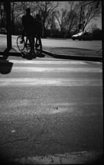 * (rumorebianco) Tags: life people bw sun film bicycle silhouette backlight 35mm shadows toycamera streetphotography lomolca parma asphalt nocrop lowfi kodaktrix400