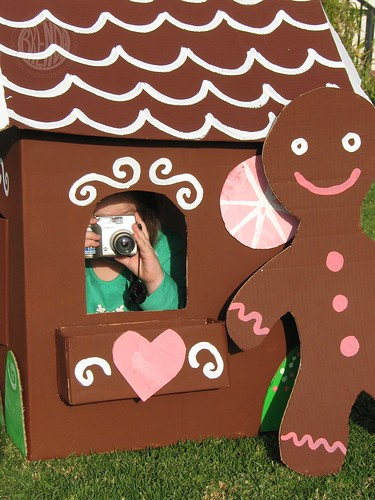 child inside a large cardboard gingerbread house with a camera in her hand