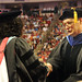 Provost Warwick Arden (right) congratulates a doctoral graduate student as he hands her the diploma.