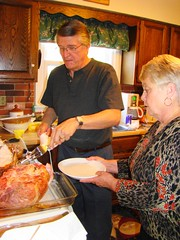 Mom and Swami carve the ham