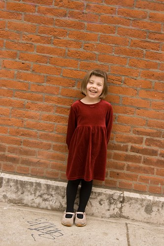 child in front of a brick wall