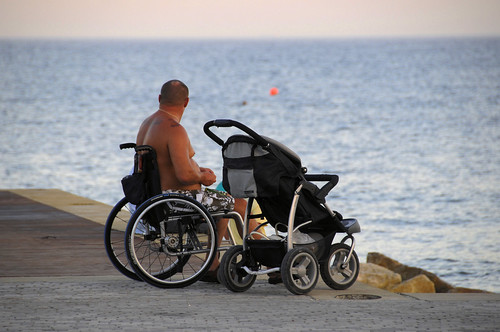 man in wheelchair sitting at jetty edge looking to the ocean. Next to him is a pram.