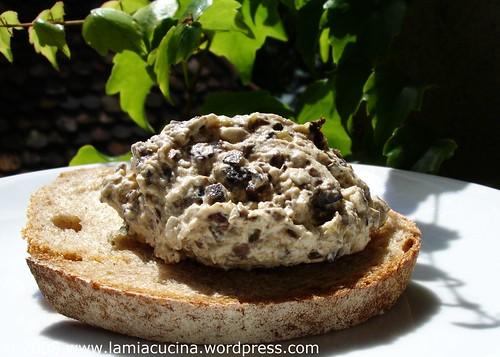 Olivenmousse auf Brot im Schatten einer Wildrebe